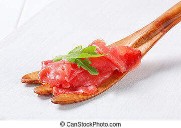 Thinly sliced raw beef on fork