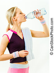 Photo of girl standing in profile and drinking water after workout on white background