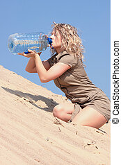Thirsty blond woman on desert