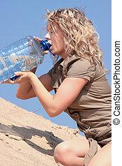Thirsty blond woman on desert