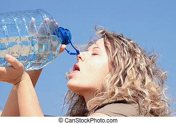 Thirsty blond woman on desert drink from big bottle of water.