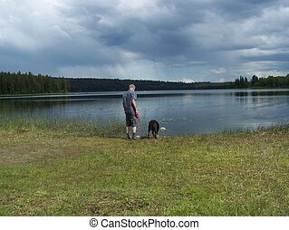 Thirsty dog with master at the lake