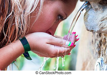 Thirsty girl drinking from outdoor tap closeup photo