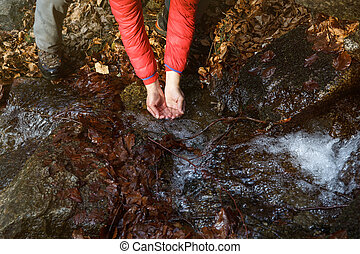 Thirsty hiker drinking water from a crystal clear spring