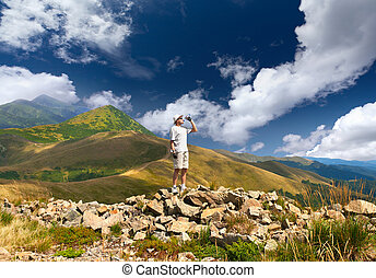 Thirsty hiker in the mountains at summer