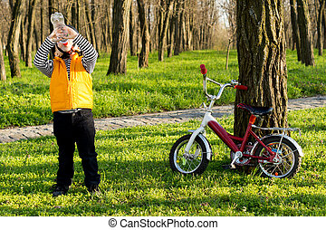 Thirsty little boy cyclist drinking bottled water