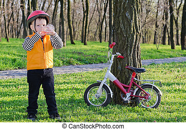 Thirsty little boy drinking water while out riding