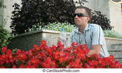 Thirsty man having a break drinking a bottle of water. Man in sunglasses and jacket. Near a lot of red flowers