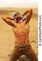 Thirsty man - Muscular man without shirt in dry desert...
