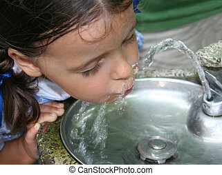 Thirsty - Pretty little girl drinking from a water fountain.