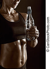 Thirsty - Torso of a young athletic woman holding a bottle...