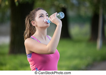 Thirsty woman drinking water to recuperate after jogging