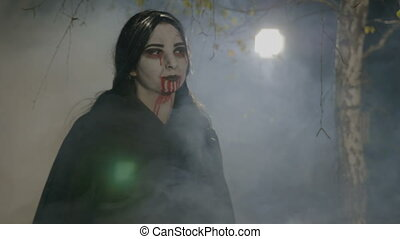 Thirsty young female vampire coming out from forest to hunt and showing her teeth on halloween night