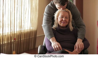 Thirty-year-old son hugs his mother looking to the camera.