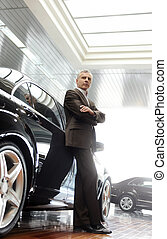 This car is perfect for me. Confident senior businessman leaning on his new car he choosed at the dealership