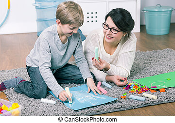 This color will be good - Young woman and boy drawing a ...