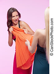 This dress is mine! It?s mine! Two angry young women trying to take away one dress while isolated on pink background