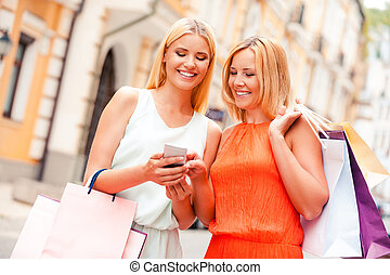 This is a nice photo! Beautiful young smiling woman holding mobile phone while her mother pointing it