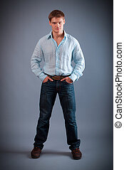 This is a photograph of a young man standing with his hands in pocket