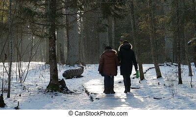 This is a shot of a young family walking in picturesque winter park with snow at sunny day.