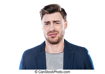 This is disgusting! Portrait of young man expressing negativity and looking at camera while standing against white background
