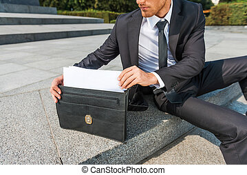 This is exactly what I need. Close-up of confident young man in formalwear taking the documents from briefcase while sitting outdoors