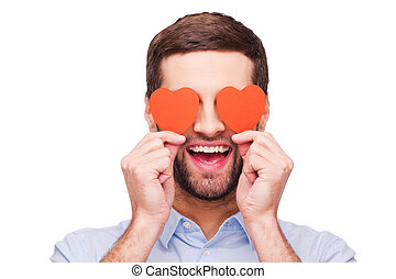This is love! Handsome young man holding heart shaped valentine cards in front of his eyes and smiling while standing isolated on white background