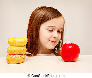 This photo depicts a young girl making decisions betwen healthy y food and unhealthy food.
