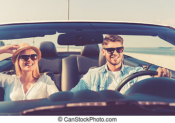This road is only for us! Joyful young couple smiling while riding in their convertible