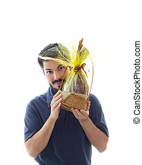 This young man's face is partially hidden by the chocolate-covered egg shell.