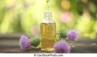 thistle essential oil in  beautiful bottle on table