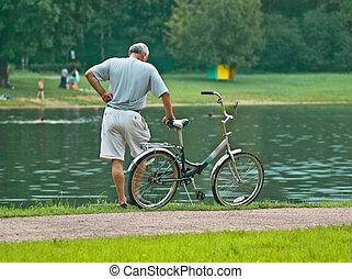 thought - senior bicyclist at park
