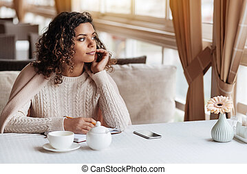 Thoughtful African American woman making notes in the cafe