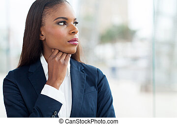 thoughtful african businesswoman looking through window