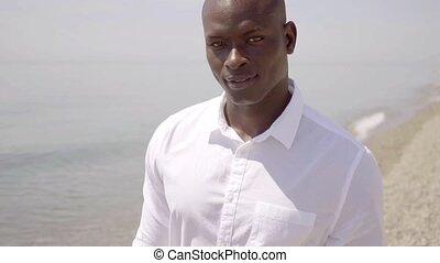 Thoughtful African man walking along the sea - Thoughtful...