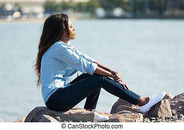 african woman sitting by the harbour - thoughtful african...