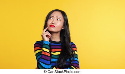 Thoughtful asian woman on yellow background. Emotion concept
