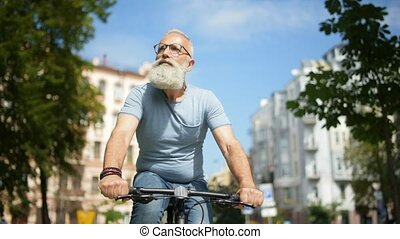 Thoughtful bearded man riding bicycle down street