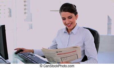 Thoughtful beautiful businesswoman using computer while...