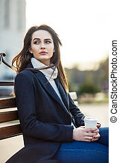 Thoughtful beautiful woman with cup of coffee sitting on a bench in city street