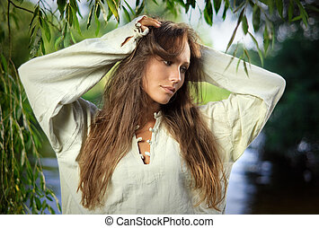 Thoughtful beautiful young woman in the willow leaves