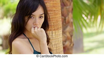 Thoughtful beautiful young woman under a palm tree
