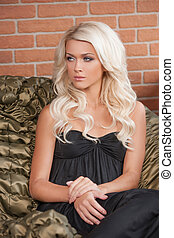 Thoughtful beauty. Beautiful young blond hair woman sitting on the chair and looking away