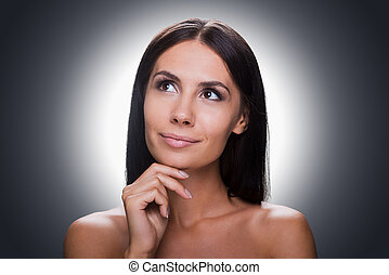 Thoughtful beauty. Portrait of thoughtful young shirtless woman looking away and holding hand on chin while standing against grey background