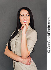 Thoughtful beauty. Thoughtful young woman looking away and smiling while standing against grey background