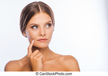 Thoughtful beauty. Thoughtful young shirtless woman touching face and looking away while standing against white background