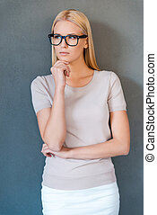 Thoughtful beauty. Thoughtful young blond hair woman holding hand on chin and looking away while standing against grey background