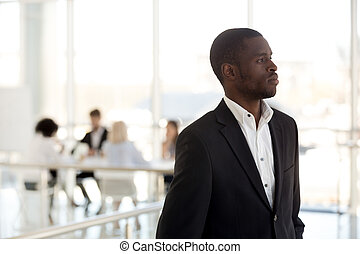 Thoughtful black employee look in distance dreaming of success