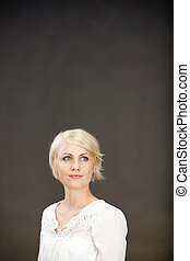 Thoughtful Blond Woman Against Gray Background