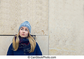 Thoughtful blond woman in warm winter clothes